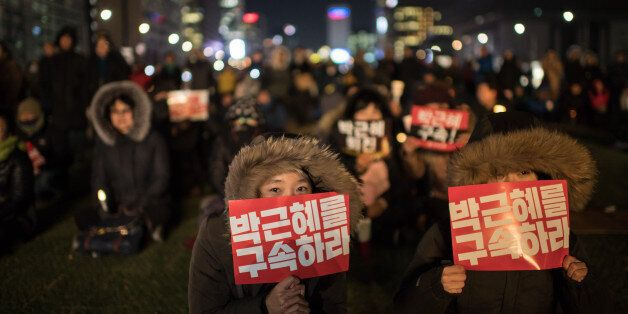 TOPSHOT - A woman hold a placard reading 'Arrest Park Geun-Hye' during a small rally following the impeachment...