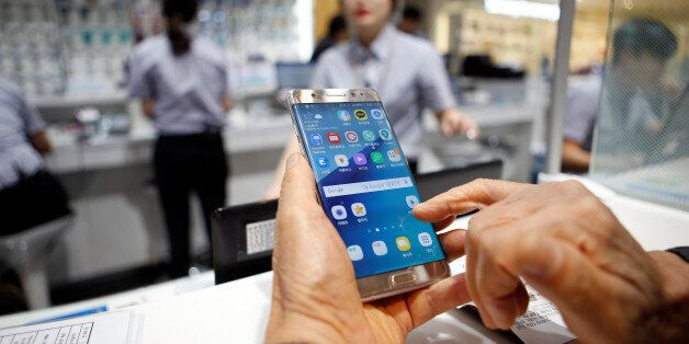 A customer uses his Samsung Electronics' Galaxy Note 7 as he waits for an exchange at company's headquarters...
