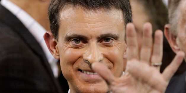 French Prime Minister Manuel Valls waves at the end of a news conference where he announced that he is...