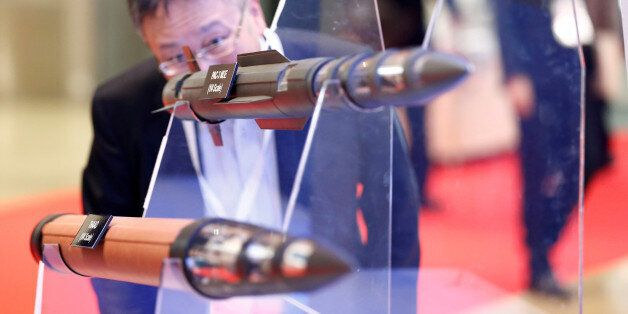 A man looks at models of Lockheed Martin's PAC-3, PAC-3 MSE and THAAD missiles during Japan Aerospace...