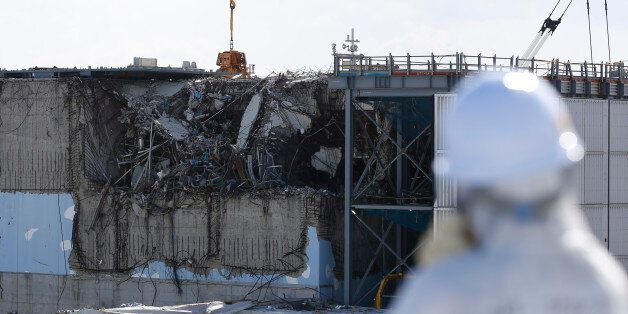 A member of the media, wearing a protective suit and a mask, looks at the No. 3 reactor building at Tokyo...