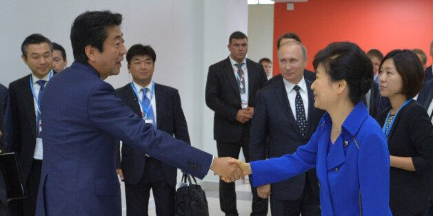 Japanese Prime Minister Shinzo Abe (L) shakes hands with South Korean President Park Geun-hye as Russian...