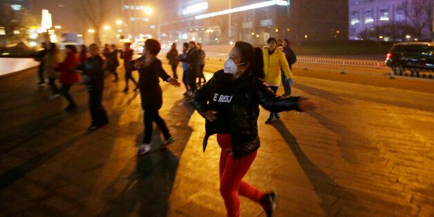 A woman wearing masks and other residents dance during their daily exercise amid the heavy smog in Beijing,...