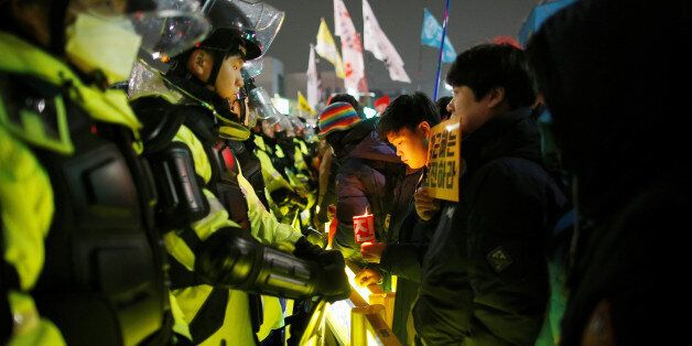 People attend a protest calling for Park Geun-hye to step down on a road leading to the Presidential...