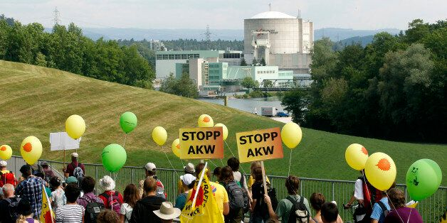 Protesters carry posters demanding a stop to nuclear power plants as they march in front of the power...