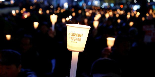 Protesters shout slogans at a candlelight protest demanding South Korean President Park Geun-hye step...