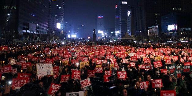 South Korean protesters hold up candles and placards during a rally calling for South Korean President...