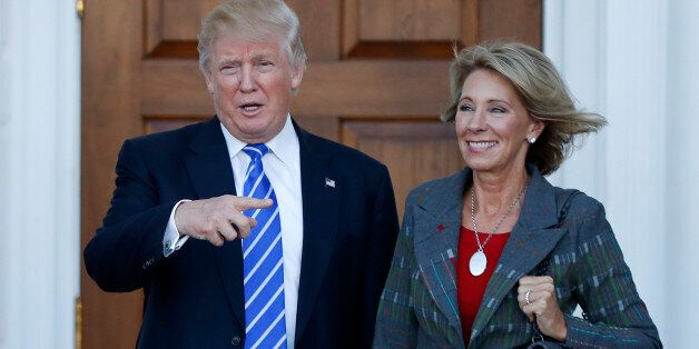 FILE - In this Nov. 19, 2016 file photo, President-elect Donald Trump and Betsy DeVos pose for photographs...