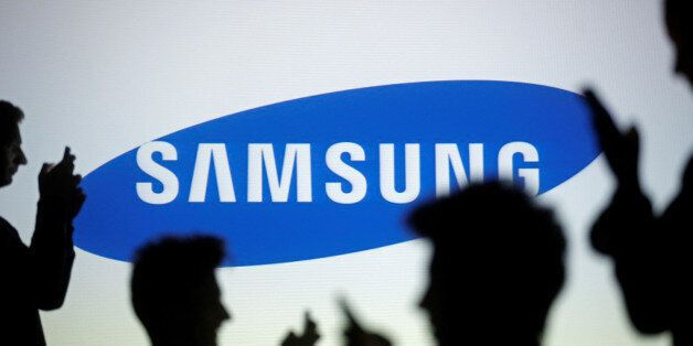 People are silhouetted as they pose with mobile devices in front of a screen projected with a Samsung...
