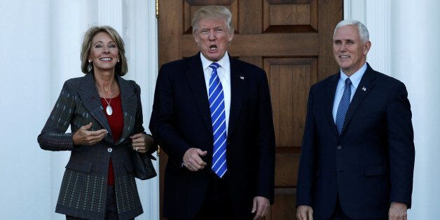 U.S. President-elect Donald Trump (C) and Vice President-elect Mike Pence stand with Betsy DeVos (L)...