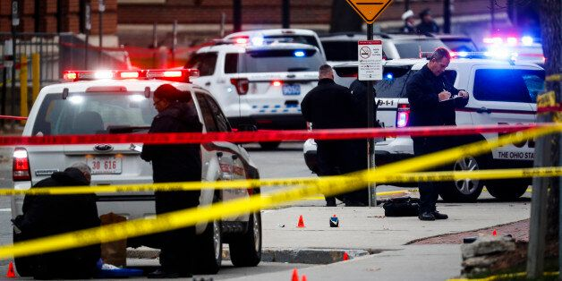 Crime scene investigators collect evidence from the pavement as police respond to an attack on campus...