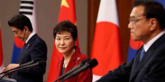South Korean President Park Geun-hye, center, looks at Chinese Premier Li Keqiang, right, as Japanese...