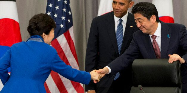 South Korean President Park Geun-hye, left, shakes hands with Japanese Prime Minister Shinzo Abe, right,...