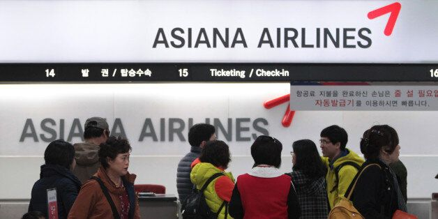 Passengers wait to buy tickets at the Asiana Airlines ticketing counter at Gimpo airport in Seoul, South...