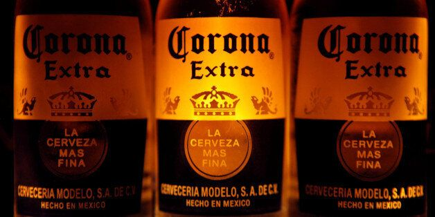 Bottles of Corona beer, the flagship brand of Group Modelo, are seen in Mexico City February 14, 2013....