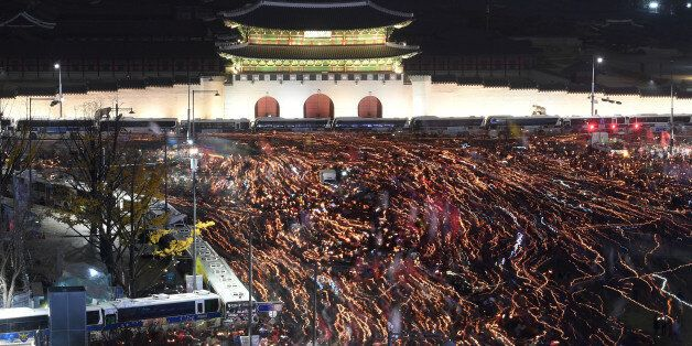 Protesters holding candles march in front of Gwanghwamun, the main gate to the royal Gyeongbokgung Palace...
