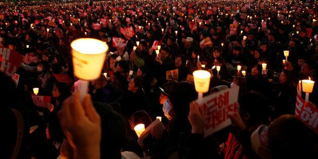 Protesters carrying lit candles shout slogans at a protest calling South Korean President Park Geun-hye...