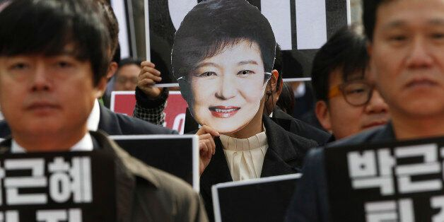 A South Korean protester wearing a mask of South Korean President Park Geun-hye marches during a rally...