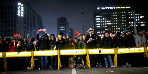 People stand behind barricades on a road leading to the Presidential Blue House during a protest calling...