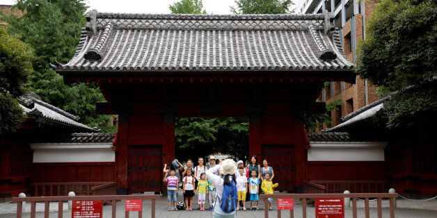 People pose for a photo in front of Akamon Gate at the University of Tokyo in Tokyo, Japan July 20, 2016....