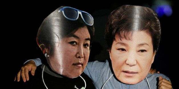 Protesters wearing cut-out of South Korean President Park Geun-hye (R) and Choi Soon-sil attend a protest...