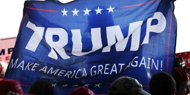 A supporter of Republican presidential candidate Donald Trump, holds up a campaign flag before Trump's...