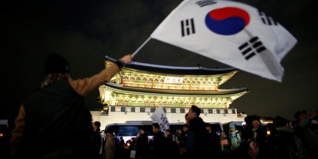 A man waves a national flag as people march toward the Presidential Blue House during a rally demanding...