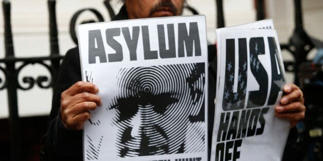 A supporter of Julian Assange holds posters after prosecutor Ingrid Isgren from Sweden arrived at Ecuador's...