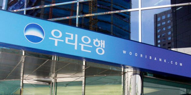 People walk into the headquarters of Woori Bank in Seoul July 20, 2010. South Korea will announce plans...