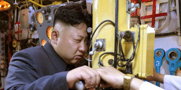 North Korean leader Kim Jong Un looks through a periscope of a submarine during his inspection of the...