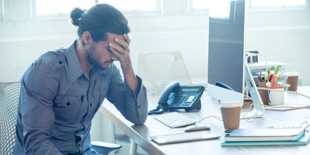 Stressed business man at the office. He is casually dressed and looking distraught. He looks very uncomfortable...