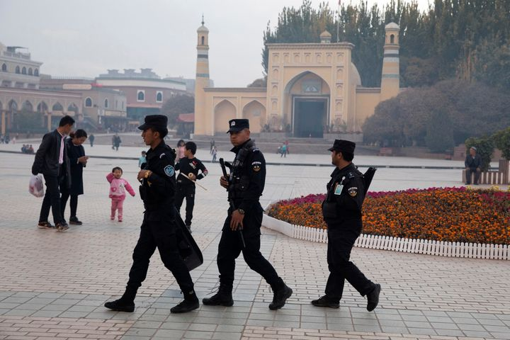In this Nov. 4, 2017 photo, Uighur security personnel patrol near the Id Kah Mosque in Kashgar in western China's Xinjiang re