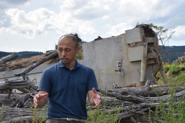 崩れた浄水場がある富里地区の説明をする宮久史さん。うしろには、杭ごと抜けて流された建物が残っている=2019年9月1日