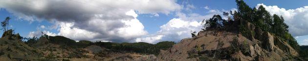 パノラマ機能で山が350m移動した現場を撮影した。右に見える山が、左から剥がれて一気にずれたという=2019年9月1日