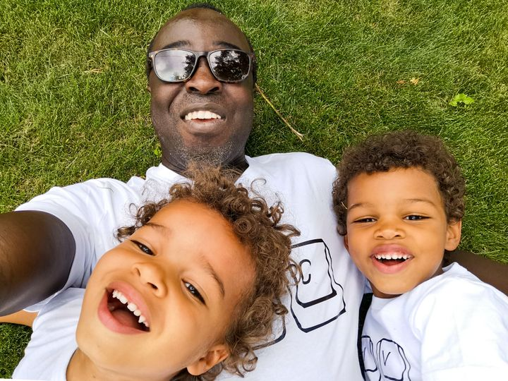 Palmer thinks it's better for kids to be conscious, even vaguely, about their race, so that they aren't left defenceless at school. (Pictured: Casey Palmer and his two sons)