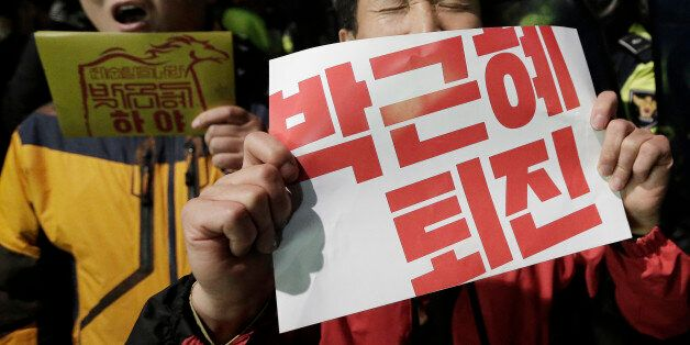 South Korean protesters shout slogans as they are blocked by police officers during a rally calling for...
