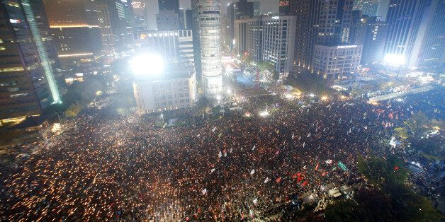 Tens of thousands of South Korean people march during a rally calling on embattled President Park Geun-hye...