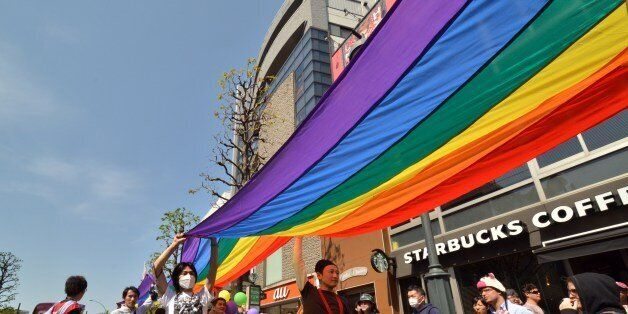 Supporters of the lesbian, gay, bisexual and transgender community (LGBT) carry a rainbow banner as they...