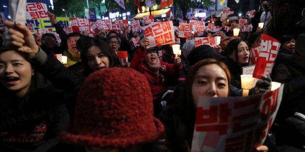 South Koreans shout slogans during an anti-president rally in downtown Seoul, South Korea, Saturday,...