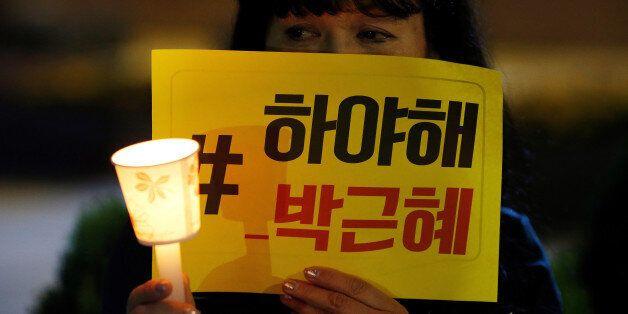 A woman attends a protest denouncing President Park Geun-hye over a recent influence-peddling scandal...