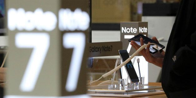 In this Tuesday, Oct. 11, 2016 photo, a visitor tries out a Samsung Electronics Galaxy Note 7 smartphone...
