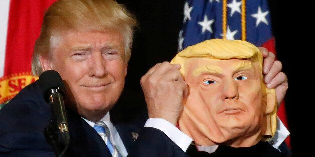 Republican presidential nominee Donald Trump holds up a mask of himself as he speaks during a campaign...