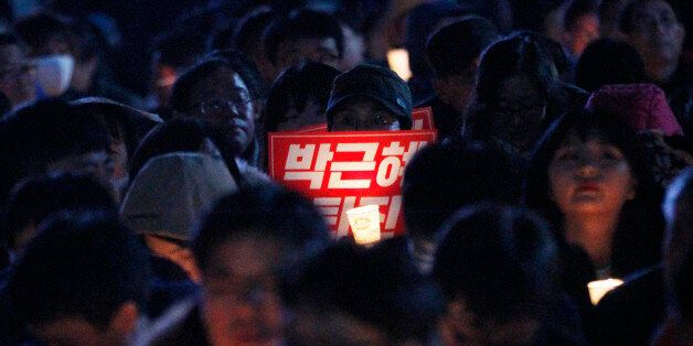 A protester holds a placard and a candle during a rally, calling for South Korean President Park Geun-hye...