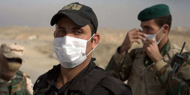 Iraqi troops wear masks as they guard a checkpoint near the village of Awsaja, Iraq, as smoke from fires...