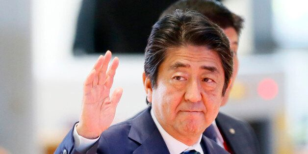 Japanese Prime Minister Shinzo Abe waves as he arrives at the National Convention Center for scheduled...