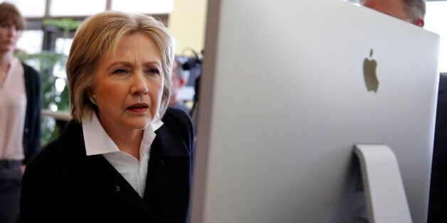 U.S. Democratic presidential candidate Hillary Clinton looks at a computer screen during a campaign stop...