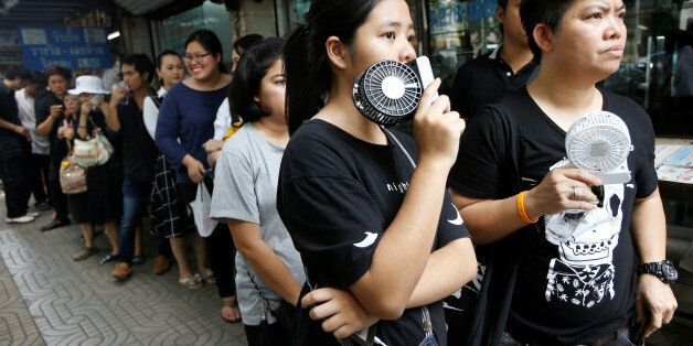 People keep cool with mini fans as they queue for commemorative 100 baht banknotes featuring the late...