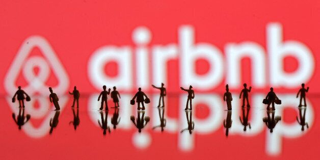 REFILE-CORRECTING GRAMMAR A 3D printed people's models are seen in front of a displayed Airbnb logo in...