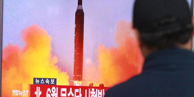 A man watches a TV news program showing a file image of a missile launch conducted by North Korea, at...