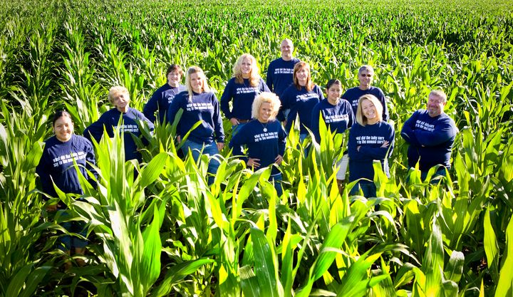 "Dani Paluchniak (second from right) and employees in a cornfield. The riddle on the fronts and backs of their shirts is: ""What did the baby corn say to the mama corn? Where's pop corn?"""